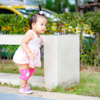 toddler on sidewalk wearing knee pads