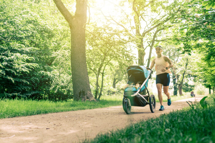 woman jogging with stroller in a park