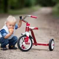 toddler boy sitting with his tricycle outside