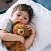 child laying on pillow with teddy bear