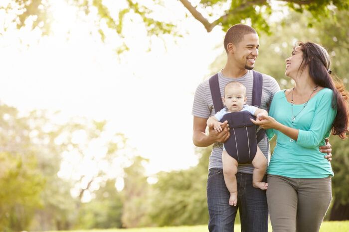 parents walking while dad wears baby in baby carrier