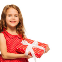 5 year old girl in pretty dress holding gift with bow