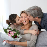 daughter and husband kissing mom and giving her a gift