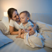mom and baby sitting in bed at night