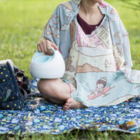 woman sitting outside pumping with breast pump bag