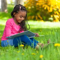 child reading a book outside in the grass