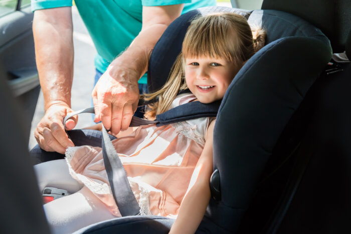 toddler getting buckled into a car seat