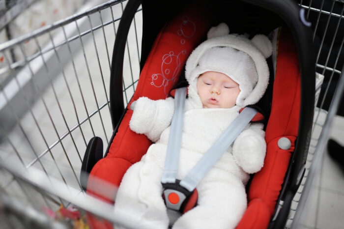 small baby in a car seat in a shopping cart