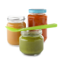 Jars with baby food and spoon on white background
