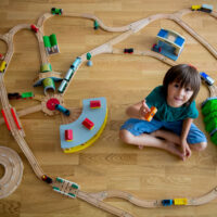 young boy sitting with large wooden train set