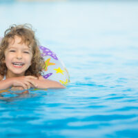 child swimming on pool float toy in water