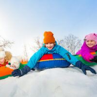 children sliding down a snowy hill on sleds