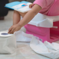 Closeup of a toddler using a small plastic toilet, grabbing for a sheet of toilet paper