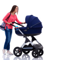 mom pushing her baby in stroller on white background