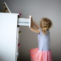 little girl climbing on dresser and nearly tipping it over