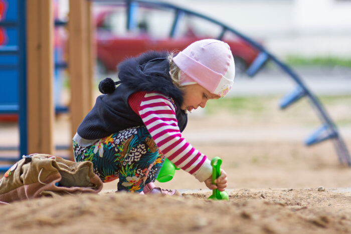 toddler playing with toy outside at a playground