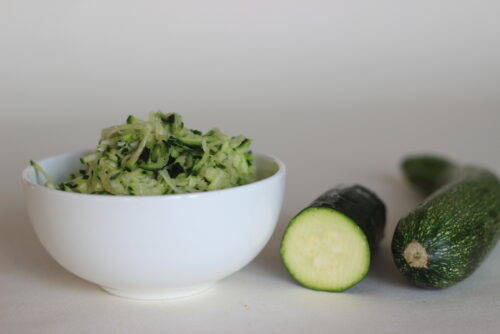 shredded zucchini in a bowl next to a halved zucchini