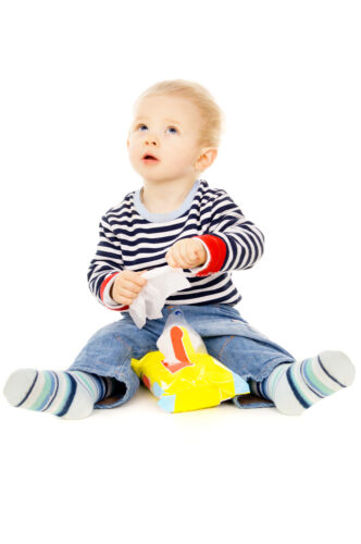 young toddler boy playing with a package of baby wipes against a white background