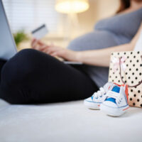 pregnant woman sitting on couch with laptop