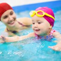 woman helping teach a baby to swim