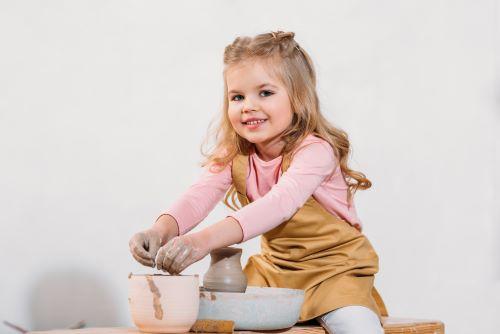 little girl at pottery wheel