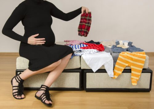 pregnant woman with newborn clothes