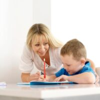 mom helping child hold pencil